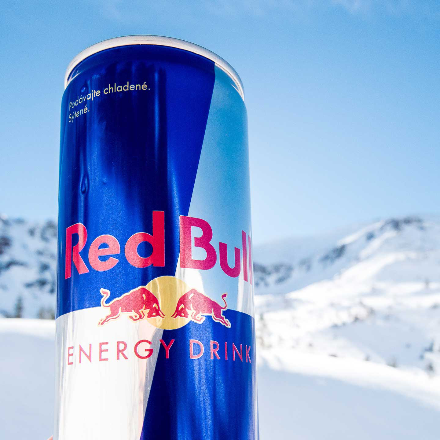 Red bull can with snowy landscape as backdrop