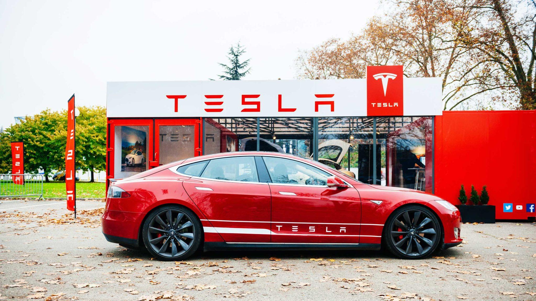 Red Tesla car outside Tesla shop